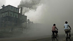 Bicyclists pass a factory in China's Hebei province. Photo credit: Peter Parks/AFP